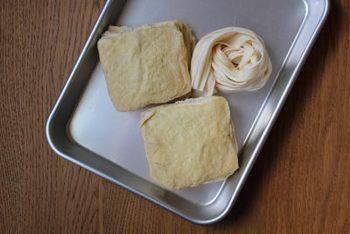 ①【俵型のおいなりさんを作るとき】   長方形、または正方形の油揚げを二つに切る。  【三角型のおいなりさんを作るとき】   正方形の油揚げを斜めに切る。 ②表面に菜箸などを転がしてから切り口から親指を入れ、穴が開かないように気をつけながら角まで開く。 ③お湯が沸騰した鍋に入れてゆでる。 ④油揚げをザル上げして、水にとる。 ⑤熱がとれたら、形がくずれないようにしながら水気をきる。 ※味付けに出汁を使う場合は、特にしっかりとゆでて油抜きし、出汁の味がひき立つようにする。