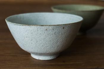 土の質感が素敵な粉引*の飯椀。黒い斑点や釉薬のたまりなどひとつひとつが表情豊かで味わい深い器です。  *粉引(こひき)とは、器のベースに白い泥をかけてつくられるもの