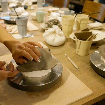 1階のショップでは、技術や製法、デザインにこだわりのある陶芸作家の作品を販売しています。2階の陶芸教室では⼿軽にオリジナルのうつわを作っていくことができます。  気軽な体験コースでは土を⽯膏の型にあてて⼩⽫や取り⽫などを作るタタラコース(5,400円)と、素焼きのうつわに銅板紙で絵柄を焼き付けるビスクコース(4,320円)があります。