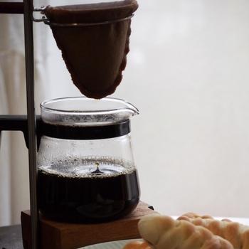 """「ネルドリップ」の""""ネル""""は、起毛している織物「フランネル」のこと。 元来は羊毛織布で作られたフィルターのことを指しますが、近年では綿や麻などが一般的です。  布製フィルターはペーパーフィルターよりも繊維の目が粗いので、コーヒーのさまざまな成分が抽出されます。油分も抽出されるのでコクのあるまろやかな味わいのコーヒーになります。"""