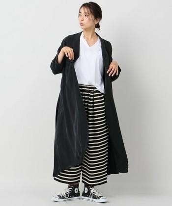 ボーダー柄のワイドパンツに、白色のトップスと黒の羽織を合わせた着こなしです。モノトーンでまとめつつ、秋の寒さにも対応できる実用性の高いコーデになっています。