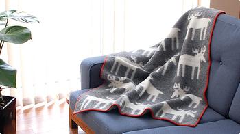 ムース(トナカイ)柄のふんわりとあたたかなブランケット。ハーフサイズで、ひざ掛けにしたり、肩に掛けたり、使い勝手のいい1枚です。無造作にソファに掛けておいても絵になりますね。