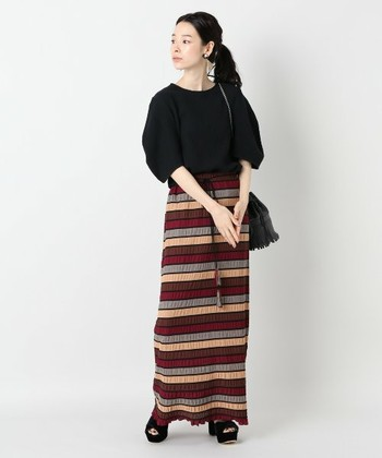 秋らしい配色のボーダーロングスカートを主役にしたコーディネート。他のアイテムや小物は黒でシンプルにまとめればすっきりと大人っぽく着こなせます。