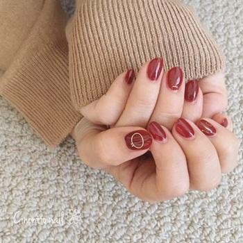シックな真紅のネイルは、あえてツヤを出し、親指と中指にゴールドをさりげなく。これからの季節、シンプルなニットとのコーディネートに大活躍してくれるネイルデザインです。