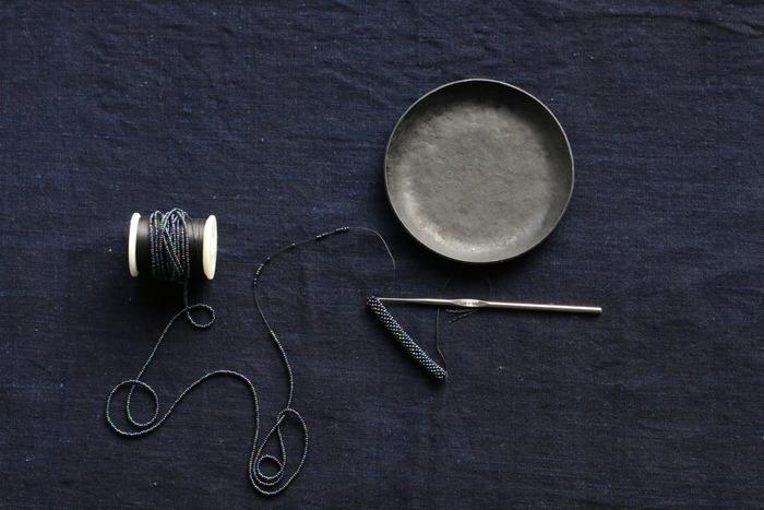 例えば、FALBEの代表作でもあるクロッシェブレスレットには、約1000粒ものビーズが使われています。長さ2mの糸に正しい配色になるよう、順序を守ってビーズを通し、ブレスレットを編み上げていくのです。熟練の職人でも4時間はかかる根気のいる作業を経て、美しいアクセサリーの数々が生み出されています。