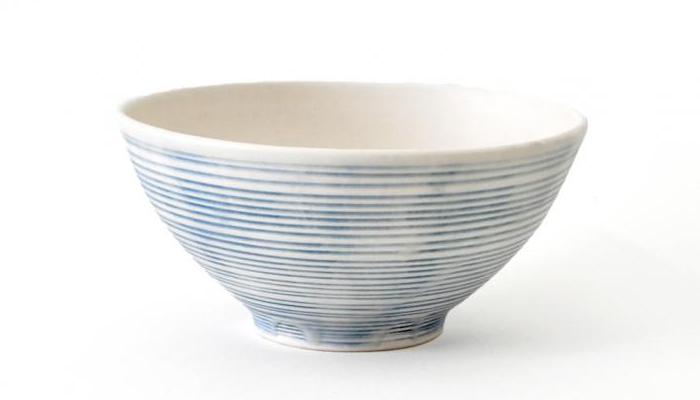 和紙のような表情の白椀と、照井さんの人気シリーズ「青線刻飯椀」は繊細な青線に乳白色の釉薬がかけられた、技のひかる器です。