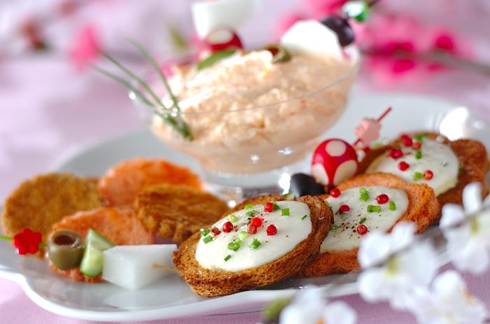 スモークサーモンのディップをつけて食べる、チーズカナッペ。レッドペッパー、アサツキでカラフルにトッピングした、華やかな一品。