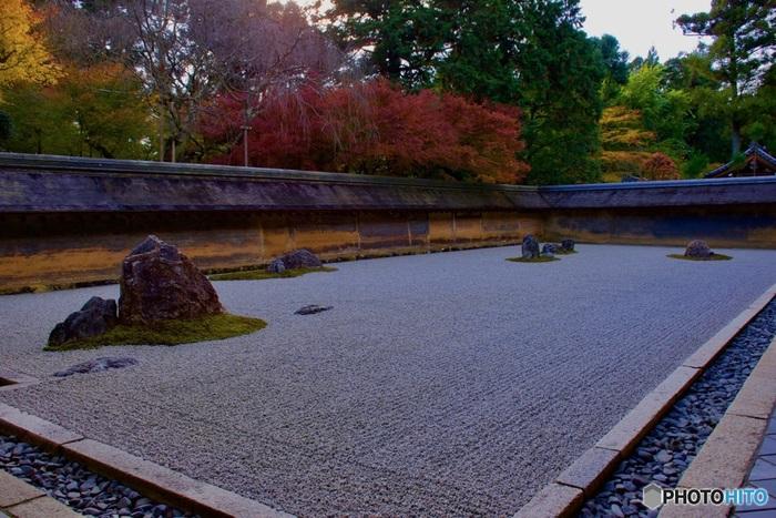 龍安寺の代名詞ともいえる方丈庭園の石庭は、イギリス女王のエリザベス2世も称讃したほど美しく、日本人が好む「わび」「さび」の風情を漂わせています。白砂利を敷き詰めた石庭を取り囲む土塀の上からは、鮮やかに紅葉した樹々が顔を覗かせ、石庭の魅力を引き立てています。