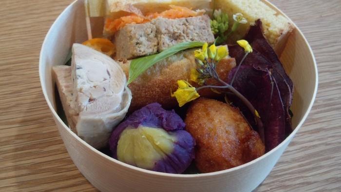 わっぱ風の丸いお弁当箱に、色とりどりの食材が綺麗に収まっています。お野菜は自然栽培/有機栽培のもので、化学調味料も一切使っていない体に優しいお弁当です。