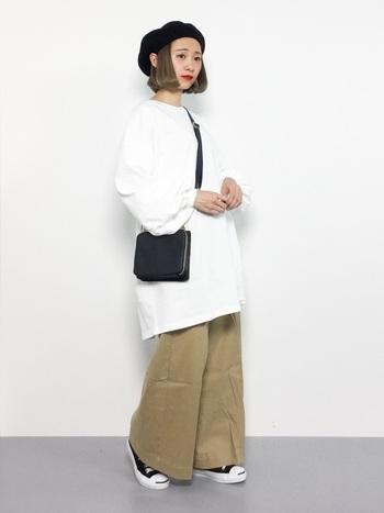 白色のゆったり長め丈トップスに、ベージュのワイドパンツを合わせた着こなし。バッグや帽子、シューズを黒でまとめてシンプルなゆるコーデに仕上げています。