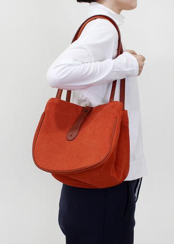 見た瞬間にパッと目が引かれるのに、モノトーンとのバランスがほどよいオレンジカラーのバッグ。シンプルスタイルの中に、きちんと秋色が映えていて、このおしゃれ感は他の色ではできません♪