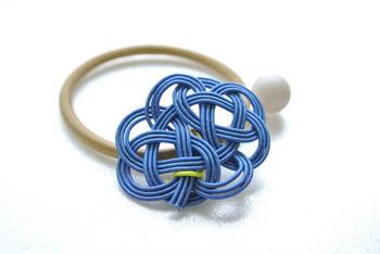 「雲結び」というオリジナルの編み方で作られた水引のヘアゴム。留め具代わりにイエローの水引が使われていて、アクセントになっています。ブレスレットとして使っても素敵。