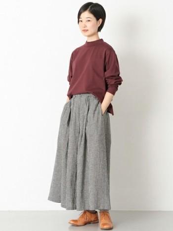 ハイネックで落ち着いた印象のボルドーのプルオーバー。チェックのギャザースカートを合わせてシンプルにするのがおすすめです。