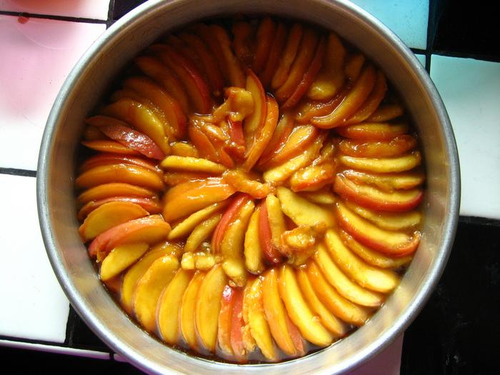 溶かしたバターを型に塗って、スライスしたフルーツをまんべんなく並べていきます。