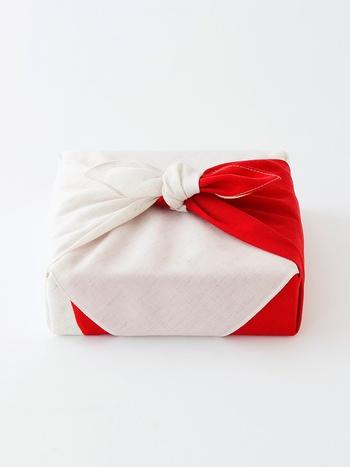 一般的な贈り物には、結び目を作る「お使い包み」をします。 リバーシブルの風呂敷を使うと裏の色も見えて、華やかですね。