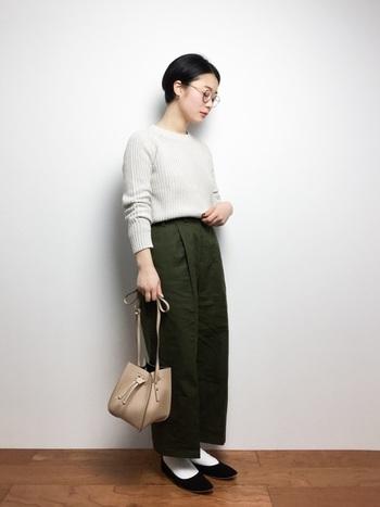 同じニットでも、足元にパンプス&靴下をプラスするとちょっぴりレトロな雰囲気に。まぁるいメガネと丸みのあるベージュのバッグで柔らかな女性らしい印象に。