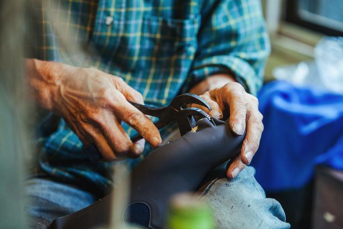 """こちらは「釣り込み」と呼ばれる作業。""""ワニ""""と呼ばれるペンチでアッパー(足の甲を覆う部分)を引っ張り、釘で木型に仮止めする"""