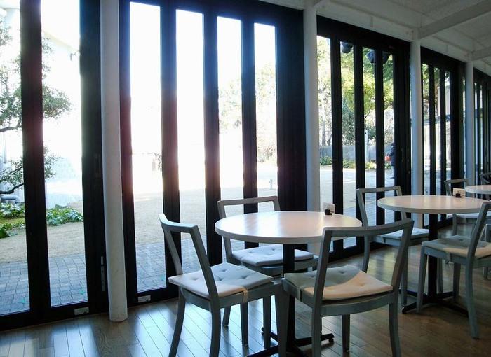 ガラス越しに陽の光が差し込む「カフェ ダール」。店内から中庭が臨めます。清潔感のある白を基調した家具とシンプルモダンな雰囲気です。