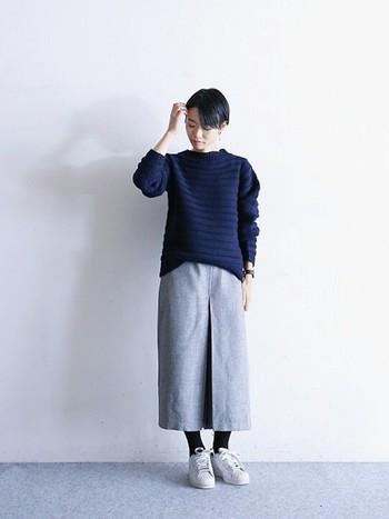 上から、紺、グレー、白とまとめた3色コーディネートは、スカート丈とセーターのバランスもポイントになります。足元はあえてスニーカーで、こなれたラフさを演出しましょう。