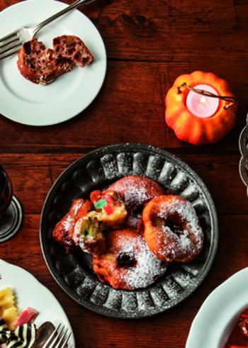 ハロウィンにもぴったりな、りんごのドーナツ。輪切りのリンゴにホットケーキミックスで作った生地をつけて揚げたものと、角切りリンゴとカラフルなジェリービーンズを混ぜた生地を油で揚げた2種類のドーナツです。