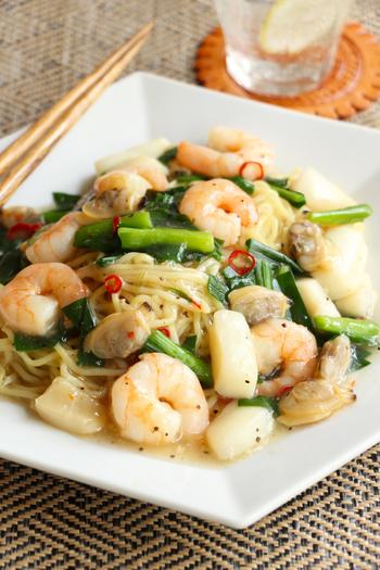 """こちらは普通の中華麺を使った焼きそば。""""焼きそば""""として売られているお手頃な麺を使ってもいいですね。ごま油でささっと炒めてお皿に盛っておきましょう。 海鮮がたっぷりでとても豪華に見えますが、シーフードミックスを使っています。餡には、にらやしょうが、にんにくなど香りのものを使って風味豊かに仕上げています。"""