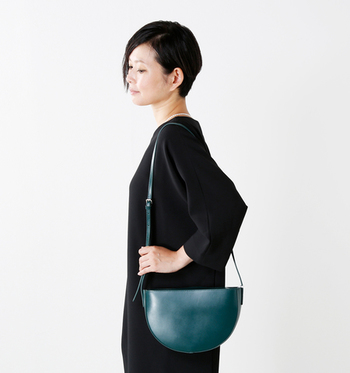 半月型の艶のあるショルダーバッグが上品な印象。シックな色合いも素敵です。
