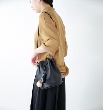 くしゃっとした巾着バッグは大ぶりなチャームが大人の女性らしいデザイン。柔らかなレザーの質感を楽しんで。