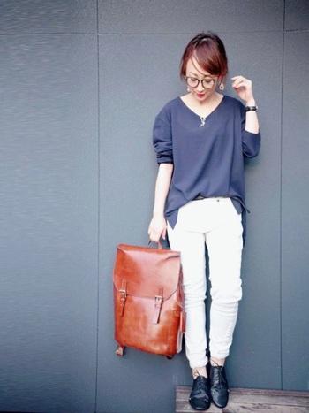ブルーグレーのニットと白デニムのシンプルなパンツスタイルに、光沢のあるブラウンのバッグでシックなアクセントを。