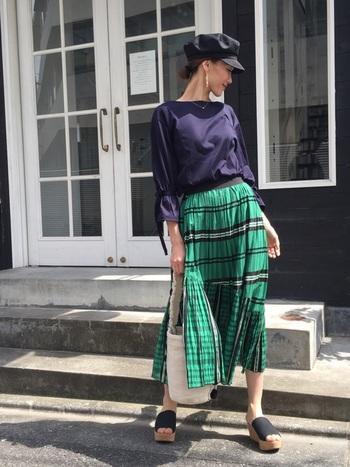バイオレットカラーのブラウスに、鮮やかなグリーンのチェックのロングスカートが印象的な辛口なスカートスタイル。スカートの色が引き立つよう、黒のキャスケットとサンダルできれいに統一感を出しています。