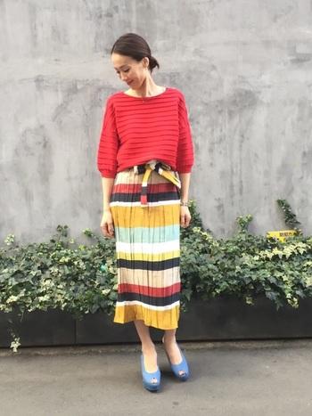 マルチカラーのボーダースカートに赤のニットを合わせたフェミニンスタイル。暖色カラーにあえて反対色のブルーシューズを合わせることで、柔らかなアクセントをプラスした技ありコーデです。