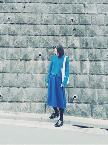 発色の良いブルーのニットとスカートの組み合わせがきれいなワントーンコーデは、足元を黒でまとめてシックに見せて。爽やかなブルーも落ち着いた印象に見せてくれます。