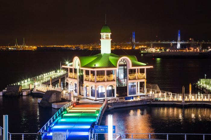 パシフィコ横浜ウィンターイルミネーションでは、横浜港のシンボルともいえるベイブリッジを背景に煌びやかな空間が出現します。虹の架け橋のような七色に輝くウッドデッキと、シャンパンゴールドに輝くターミナルが織りなす夜景の美しさは格別です。