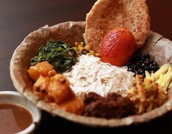 「ネワール民族の伝統料理、サマエボウジ」は、千飯、スパイシーラム肉、じゃがいもの漬物、大豆炒め物、スライス生生姜、ほうれん草炒め、ゆで卵、漬物、バラをワンプレートした個性的な盛り付けも気になります。