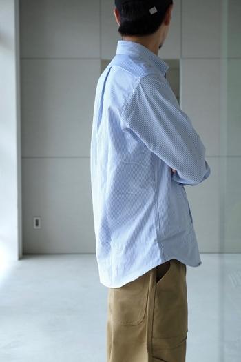 爽やかなストライプのシャツに、ゆったりとしたパンツを合わせたコーディネート。シャツをラフに着こなしています。