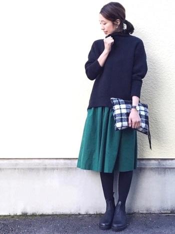 ディープグリーンのスカート以外はタイツまで全て黒で統一した、一点投入コーデで大人っぽく。季節を感じさせるフワフワのチェックのクラッチバッグがコーデにメリハリを与えています。