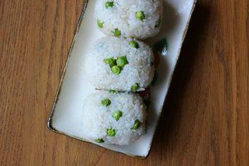 鮮やかな緑が見た目も可愛いグリンピースご飯。 実を出汁(だし)びたしにしておいて、薄く下味をつけて炊いたご飯と混ぜて作ります。