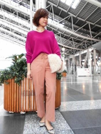 アクティブなパンツスタイルも優しいピンクコーデで女性らしく。ふわふわもこもこのクラッチバッグもアクセントになっています。
