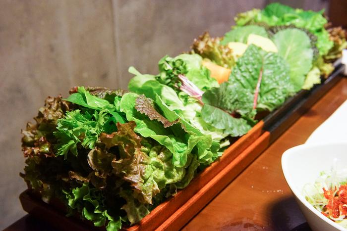 """「くるむ サンパ店」は、本場韓国のように様々な種類の野菜で""""くるむ""""焼肉サムギョプサルを頂けるお店です。  こちらで食べるべき「15種類の野菜と韓国焼肉セット」は、15種類の野菜と16種類から選べるお肉のセットです。店員さんが焼いてくれたお肉を薬味やキムチと一緒に野菜で巻いていただきます。野菜が新鮮で美味しくたくさん食べてしまい、野菜のおかわりもできます。残った野菜は野菜ジュースかスムージーにしてくれ、それもとっても美味しいのです。 ランチタイムの「15種類の野菜と韓国焼肉セット」は、さらに韓国料理が1品ついてディナーよりリーズナブルな価格になっているので、開店直後から行列が出来ます。"""