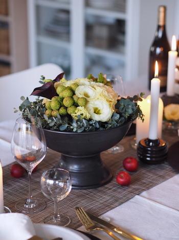 グリーン系の植物やお花にキャンドル、小さな赤いリンゴを散りばめて、クリスマスらしい雰囲気。ナチュラルにクリスマスの雰囲気が出せる素敵なアイデアです。
