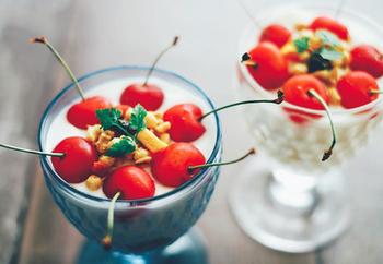 ヨーグルトを入れた器の上に、お好みのトッピングとさくらんぼを並べてパフェに。さくらんぼの茎が外に出るように並べると華やかになります。