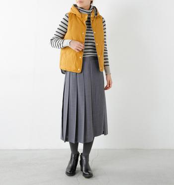 きれいめコーディネートでもダウンベストは似合います。ロングスカートとブーツの秋冬アイテムで季節感を合わせて。