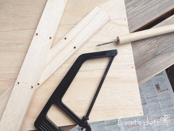 はじめに木製角材6本のうち、2本をウッドフレームの縦(長い方)の長さに合わせてカットします。次にカットした2本の木材に、棚を付ける位置に目印をつけ、写真のようにネジをつけやすいようにキリで穴を開けます。