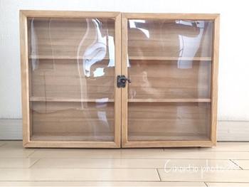 ウッドフレームの裏の留め具を取り外したら、材料の木材すべてに水性ニスを塗ります。ニスが乾いたら接着剤と木ネジで棚を組み立て、ウッドフレームは透明のプラスチック版とフレームを接着剤で張り合わせます。組み立てた棚とウッドフレームを蝶番で固定し、正面にアーチ型金具、底に脚用の木材を取り付けたら完成です!
