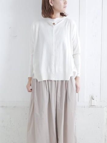 白のカーディガンに、薄めのベージュスカートを合わせた着こなしです。カーディガンは前をぴったり閉めても、開けてインに白やベージュのインナーを合わせても、おしゃれにまとまります。