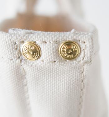 扱いやすさとバランスを重視した少し短めのハンドルや、ブランドロゴが刻印されたオリジナルの真鍮ボタンがポイントです。