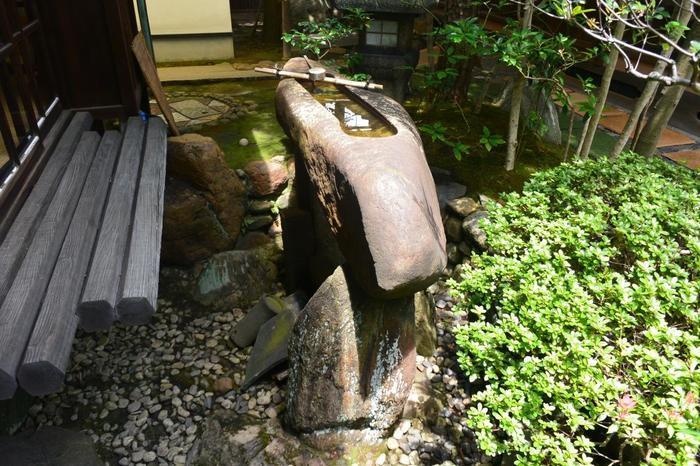 """""""島""""に見立てた家屋を支える岩、手水鉢、影石、灯籠等など。石の配置や使い方が実に巧みです。卓越した才能をもつ施主と庭師によって生まれた見事な庭園です。【鞍馬石で造られた「一文字手水鉢」】"""