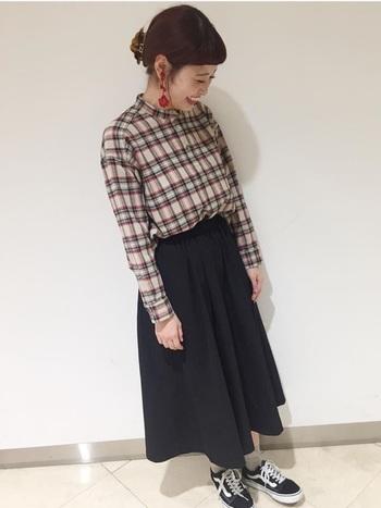 チェックシャツにダークトーンのスカートを合わせた着こなし。足元もスニーカーでカジュアルな印象が強めですが、大ぶりピアスを合わせることでガーリーな印象に変わります。