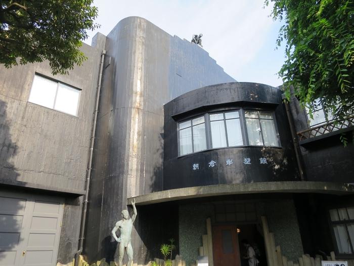 日暮里駅から徒歩5分、「朝倉彫塑館」は、彫塑家・朝倉文夫が昭和10年から39年までアトリエ兼住宅として使っていた建物です。入口付近に彫刻がありますが、屋根の上にも人影が…。