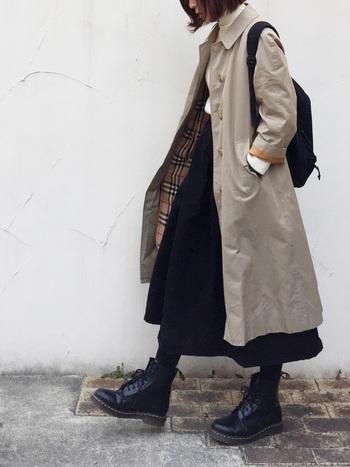 ハリ感のあるチノのロングスカートとステンカラーコートの組み合わせに、黒リュックとブーツで引き締めたブリティッシュな着こなしです。