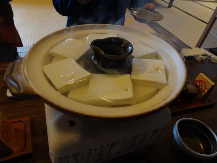 国内産の厳選大豆と白川の湧水で作られる自家製豆腐は、硬すぎず柔らかすぎず、程良い硬さ。徳利で温められた特製の秘伝ダレと薬味で頂きます。豆腐の味が濃く、円やかな味わい。大豆の旨味、甘味が感じられると評判です。